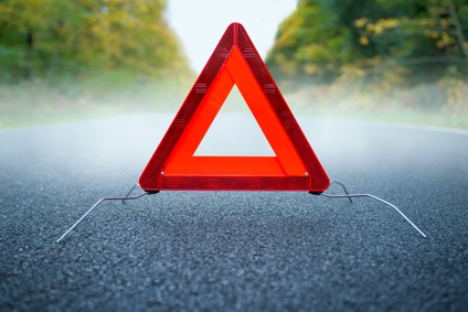 Caution fog - Warning triangle on a foggy road.