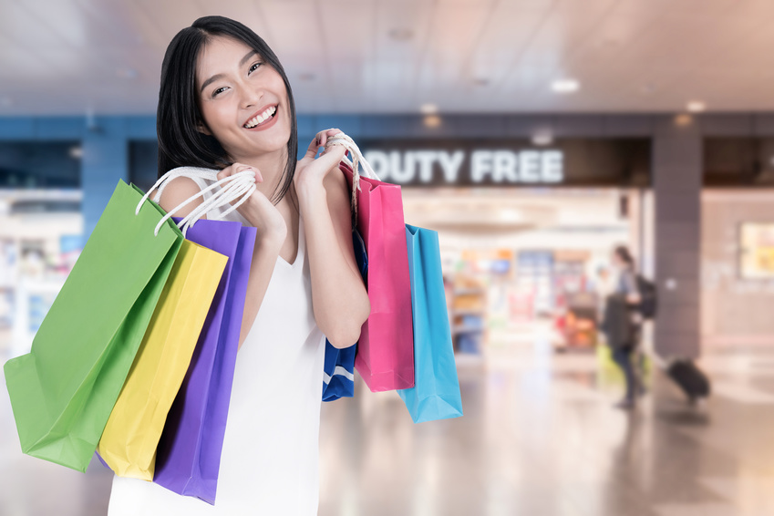 Beautiful Asian woman with shopping bags in duty free in International Airport before departure. Sale, shopping, tourism and happy people concept
